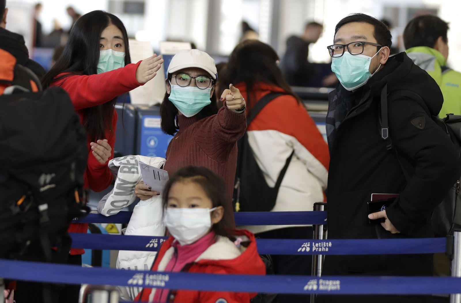 Cestujúci, ktorí čakajú na bezpečnostnú kontrolu do Šanghaja, majú na tvári ochranné rúška na medzinárodnom letisku Václava Havla v Prahe v pondelok 27. januára 2020.